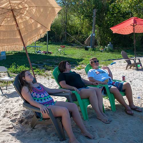 Three people laying in the shade on the sandy beach.